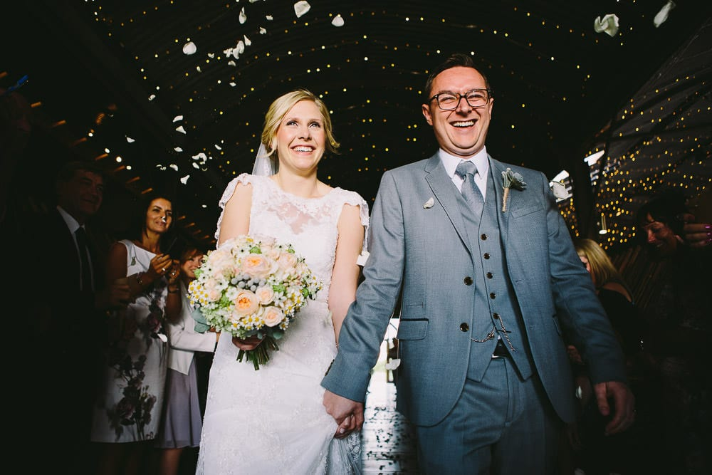 Bride and groom walking through the confetti at Cripps Stone Barn