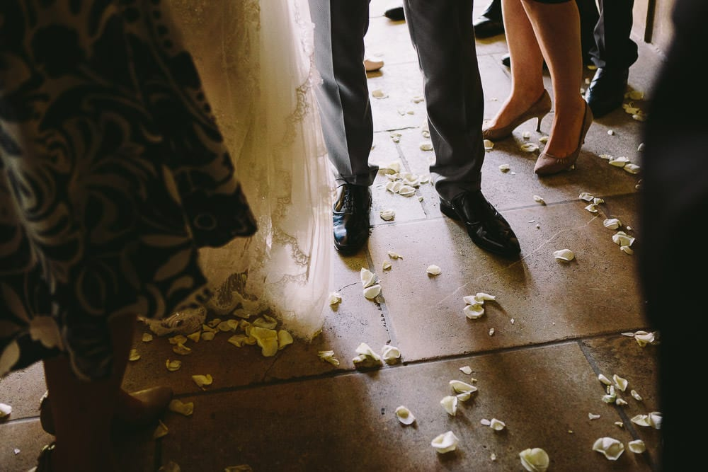 Confetti at the feet of the bride and groom in the Dutch barn at Cripps Stone Barn