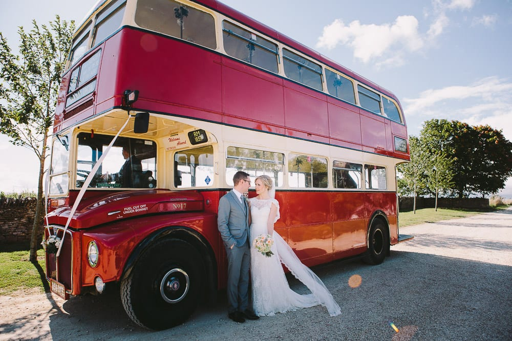 Bride and groom standing next to vintage bus outside Cripps Stone Barn