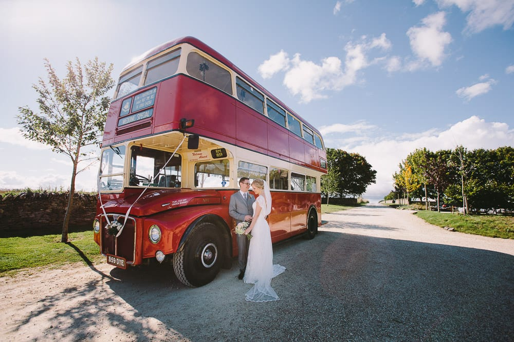 Bride and groom standing next to the vintage routemaster bus at Cripps Stone Barn
