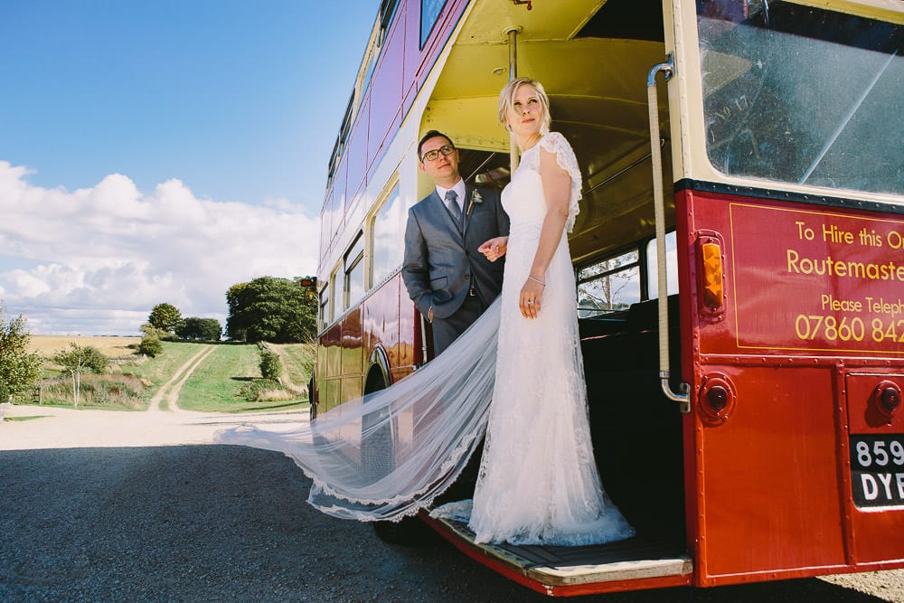 Bride and groom at the rear of the vintage bus outside Cripps Stone Barn