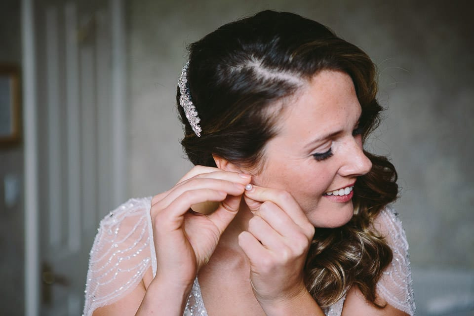 Bride putting her earrings in