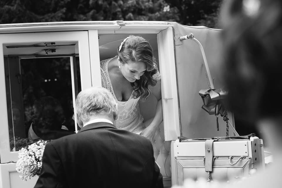 Black and white image of bride getting out of carriage