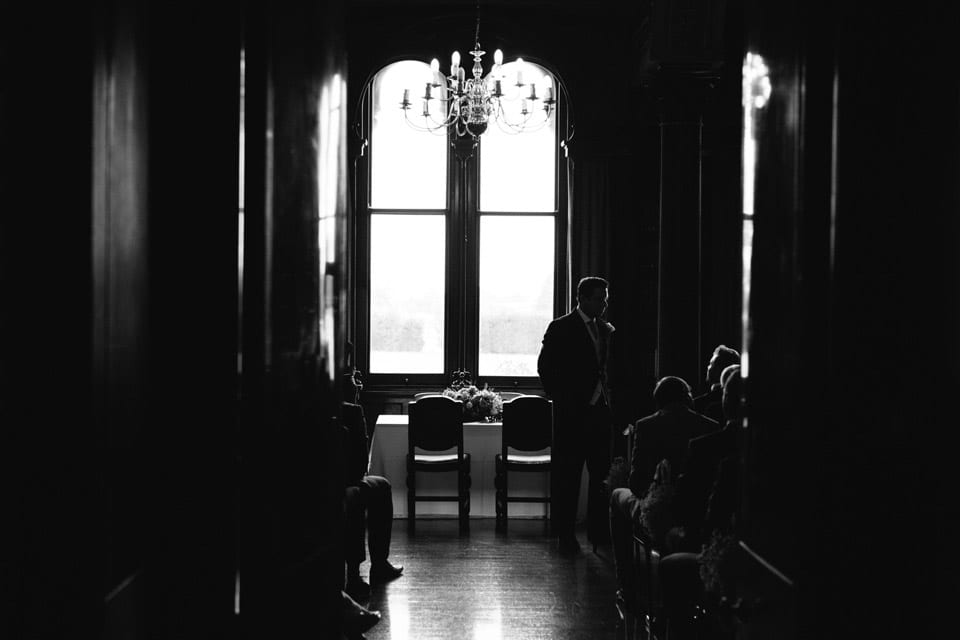 Black and white image of groom waiting for his bride