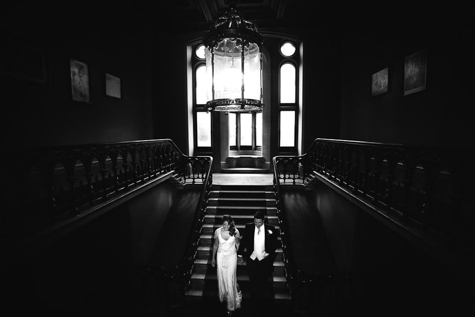 Black and white image of bride and groom on grand staircase