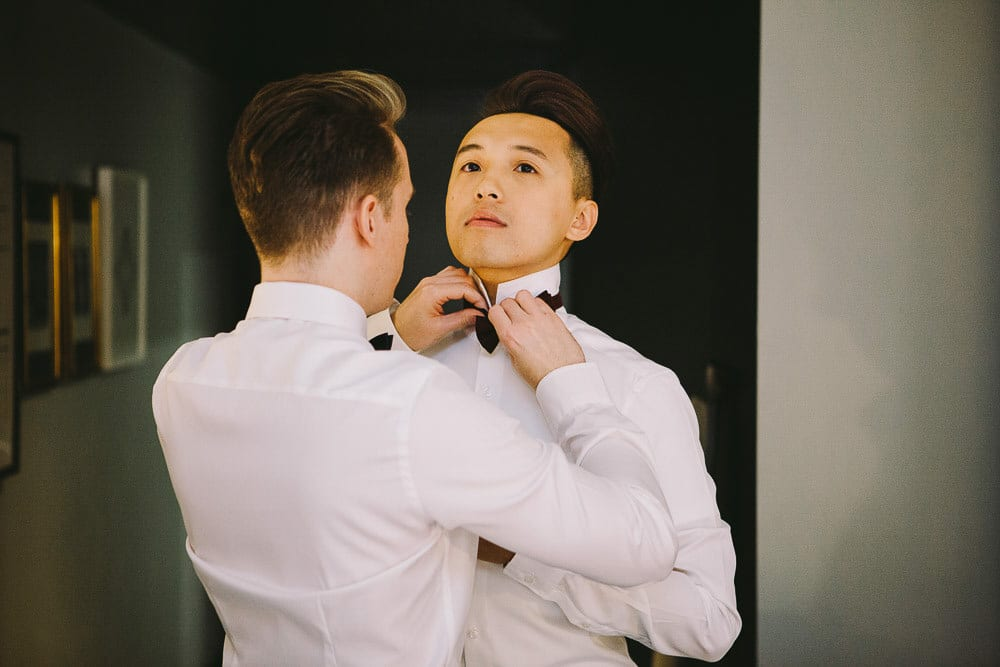Groom fastening the other grooms tie in the hotel room at The Hoxton London