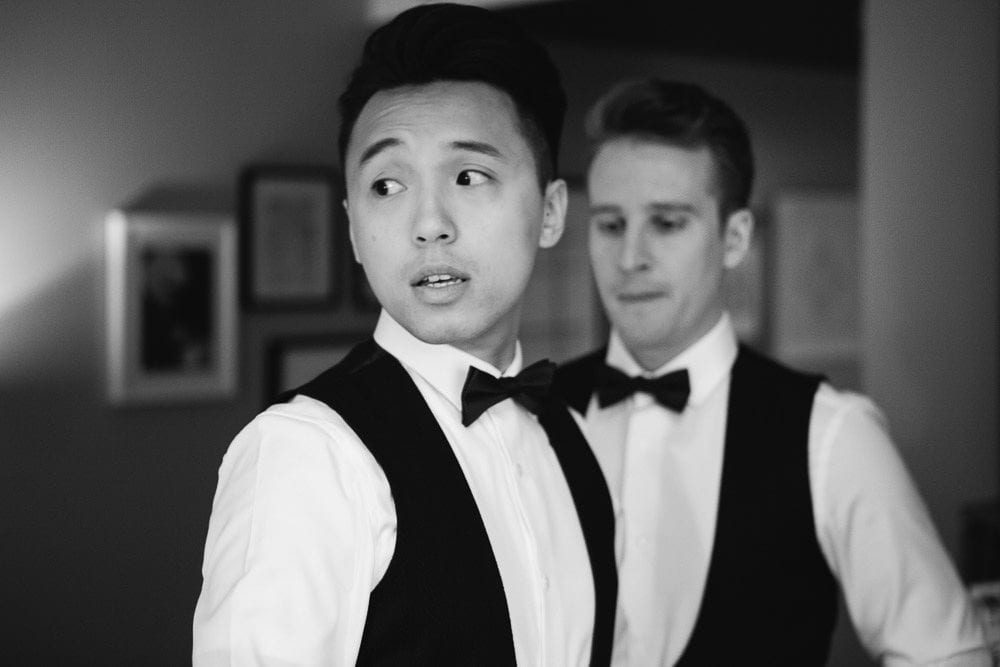 Both grooms looking in the mirror in their hotel room at The Hoxton London