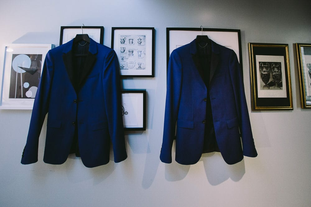 Grooms jackets hanging on picture frames in the hotel room