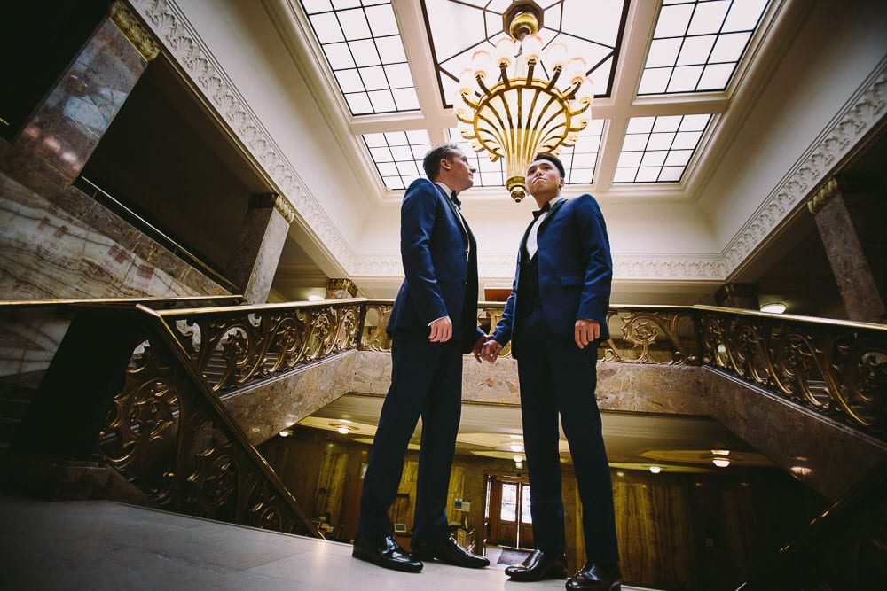 Both grooms standing on the marble steps inside Wandsworth Town Hall
