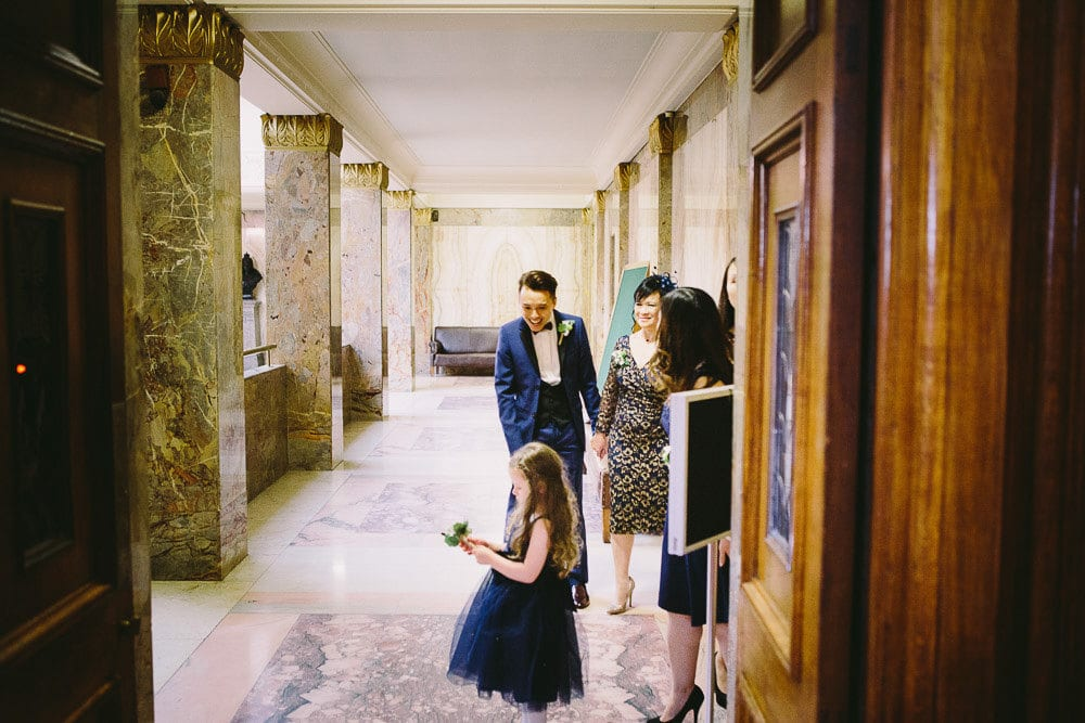 Groom with his mother and flower girl waiting to enter the Grand Chamber for their wedding at Wandsworth Town Hall