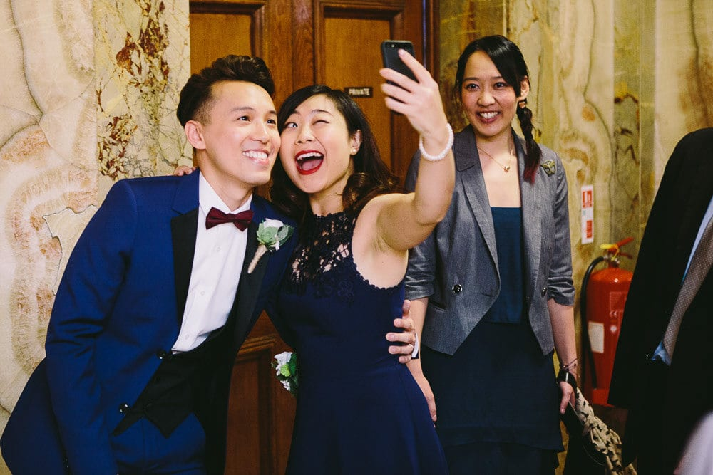 Groom and bridesmaid taking a selfie in the hall at Wandsworth Town Hall
