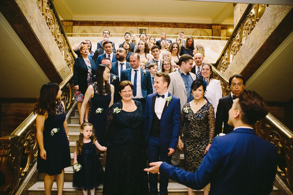 Everyone gathering on the stairs for the group wedding photo at Wandsworth Town Hall