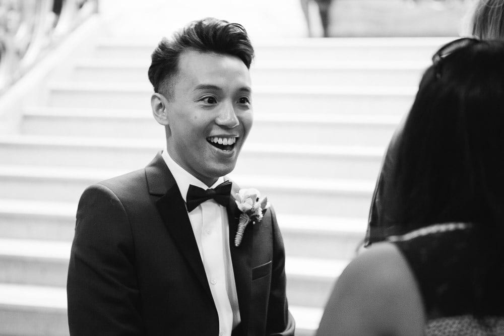 Groom laughing with guests in the lobby at Wandsworth Town Hall
