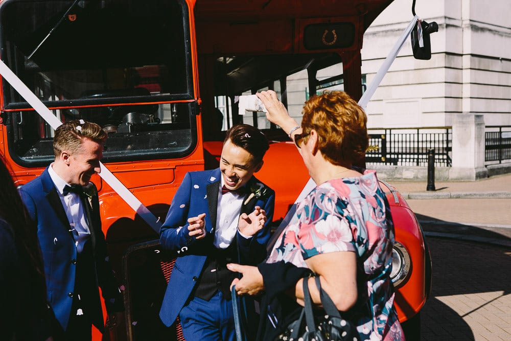 Grooms getting showered with confetti by vintage double decker bus