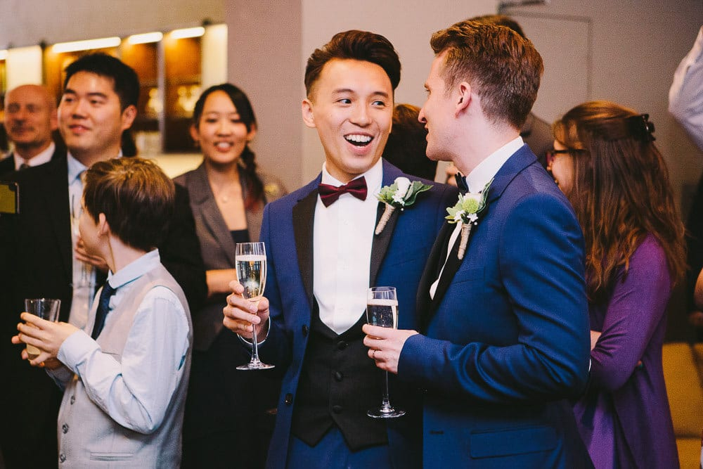 Grooms having a laugh and a drink during the speeches at The Hoxton London