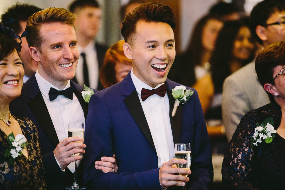 Grooms laughing at speeches at The Hoxton London