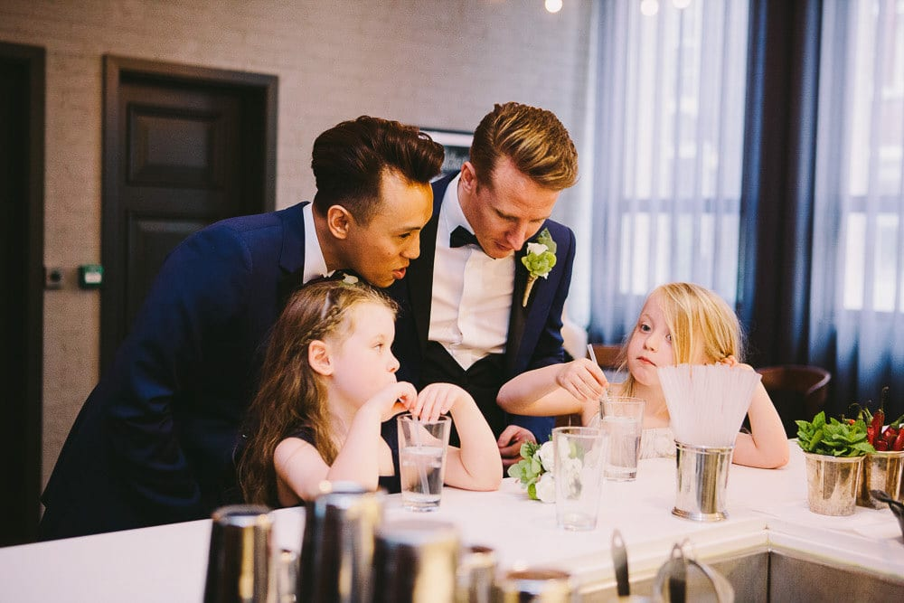 Both grooms talking to flower girls in The Hoxton London