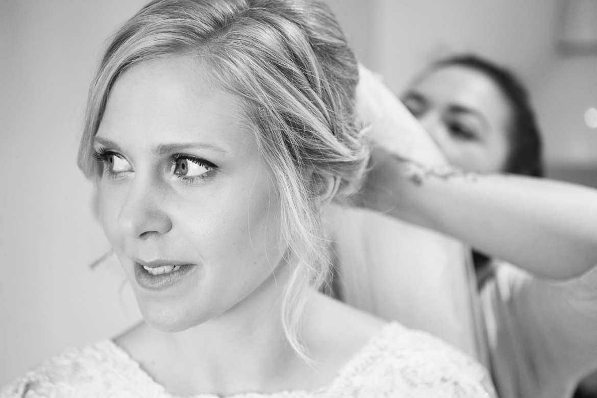 Black and white image of bride having her veil put on