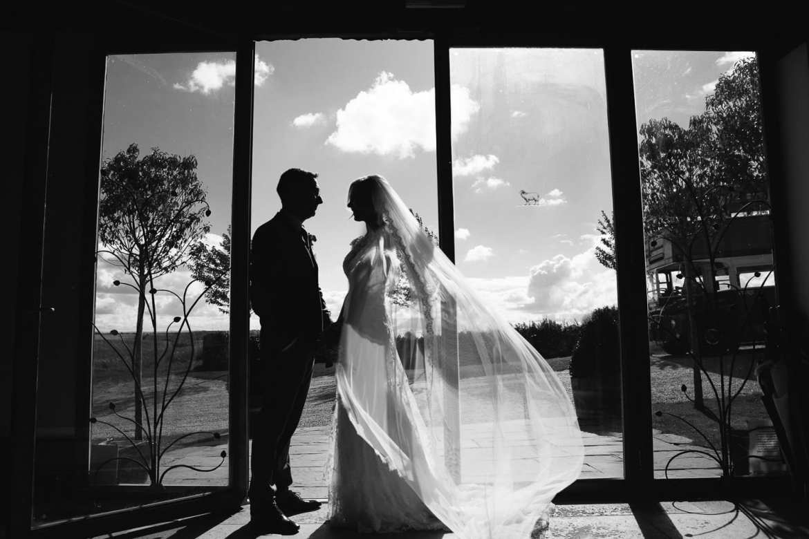 Black and white silhouette of couple at entrance to venue