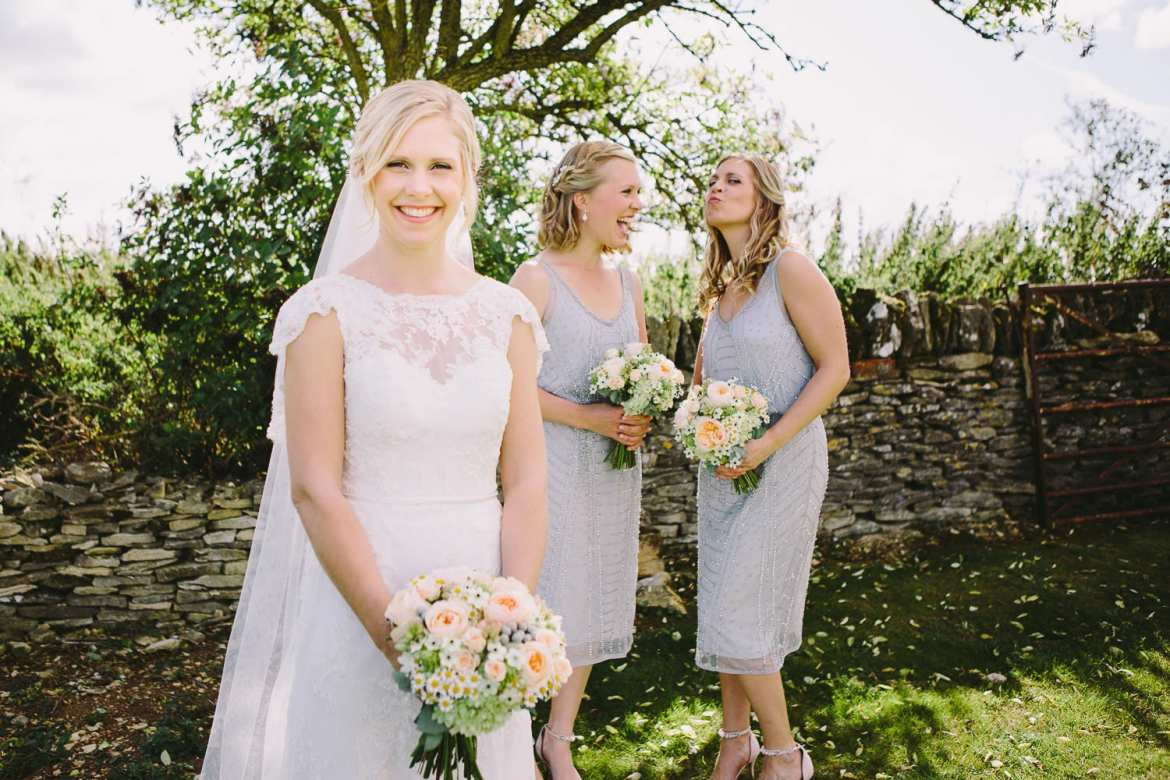 Bride with her bridesmaids pulling faces behind her