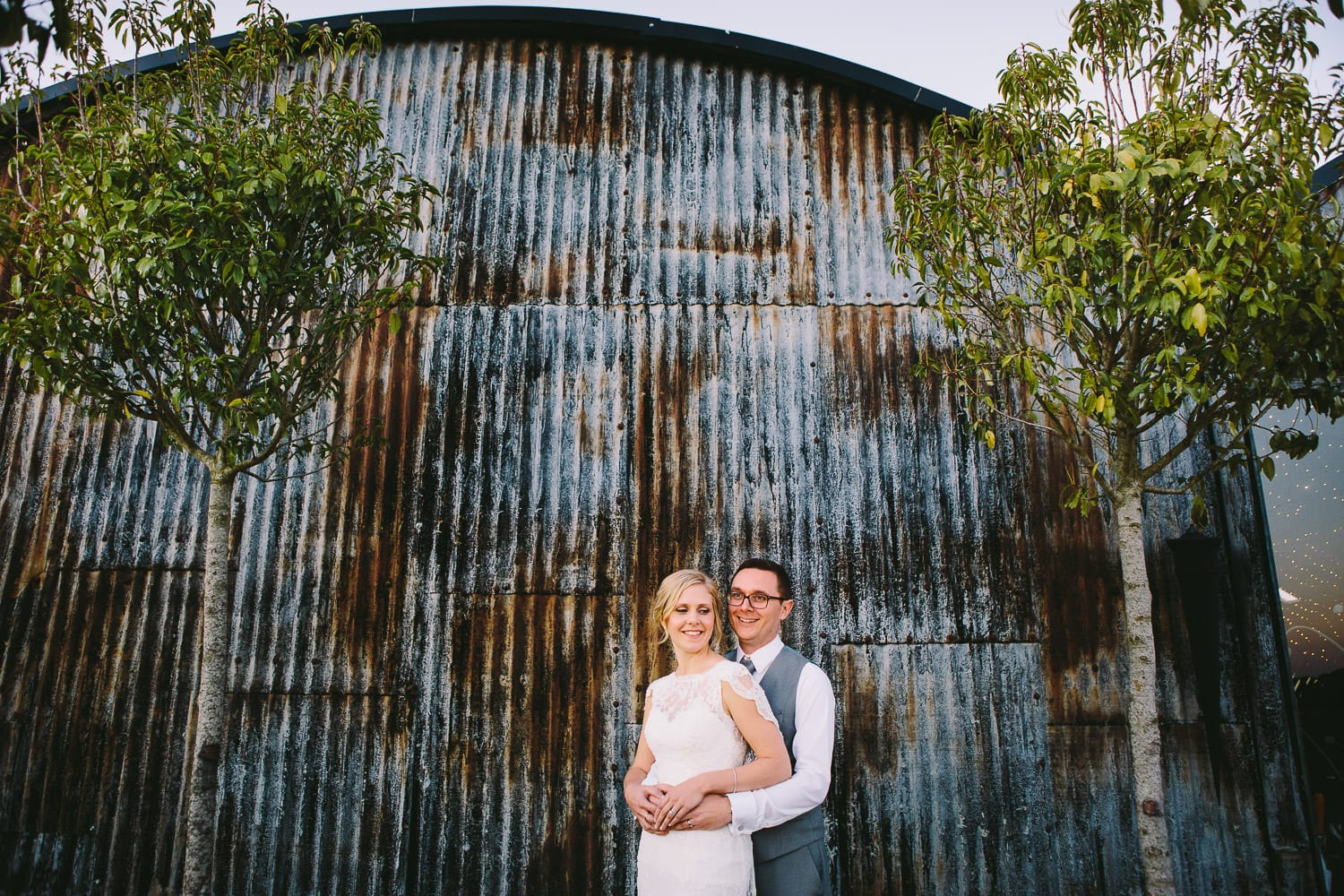 A bride and groom pose in front of the dutch barn