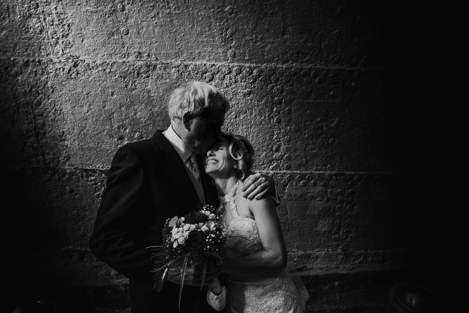 A back & white portrait of the bride and groom under the hull