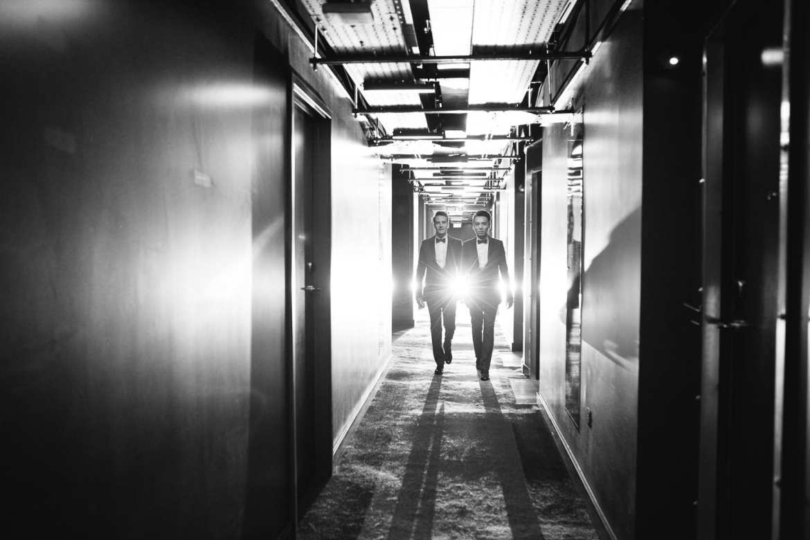 Black and white image of couple walking down corridor
