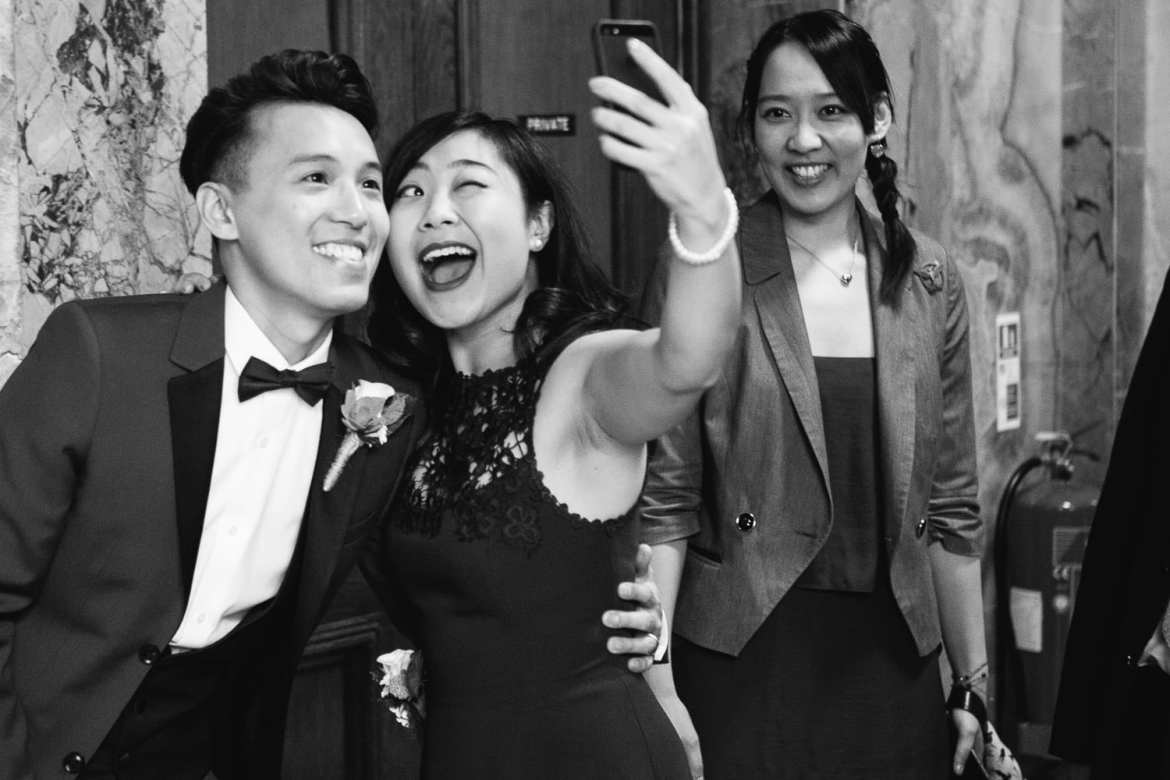 Black and white image of groom with friend taking a selfie