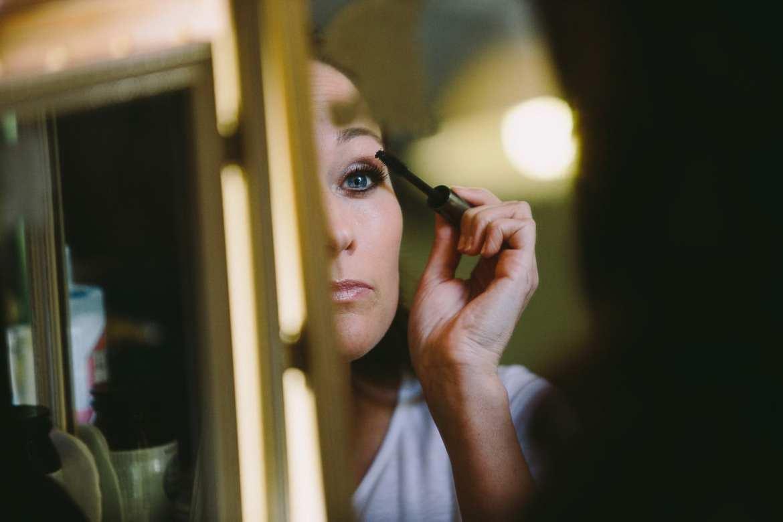 Bridesmaid applying her makeup in mirror