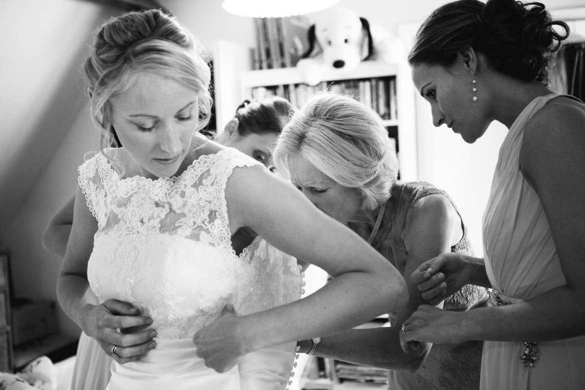 Bride getting into her dress in black and white