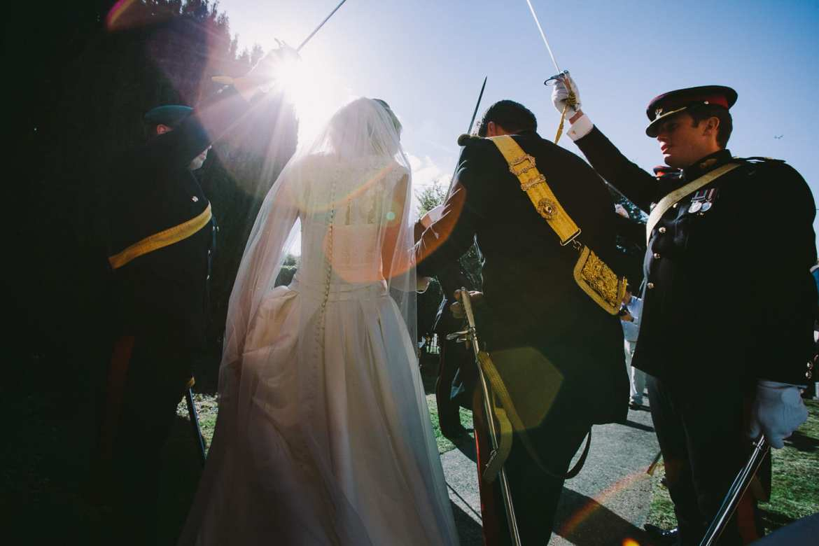 Bride and groom leaving church with military honour guard