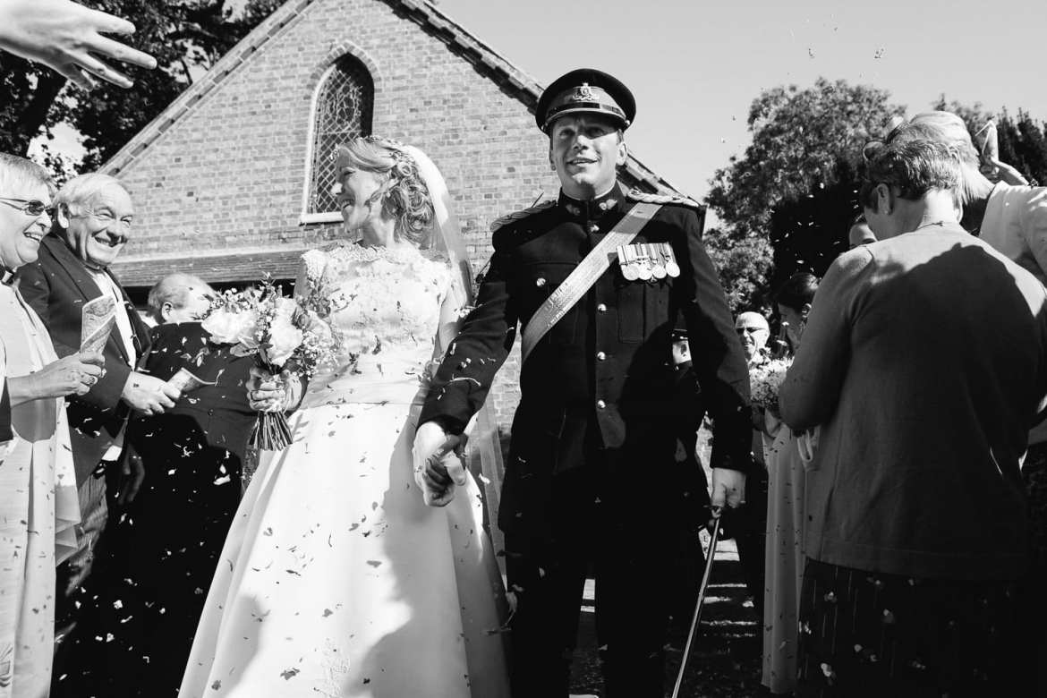 Black and white confetti image of couple leaving church