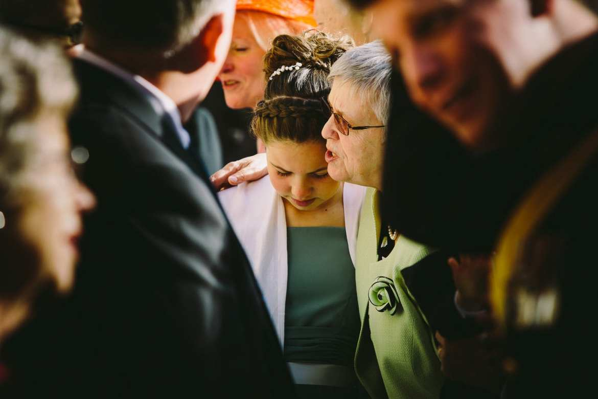 Bridesmaid getting a hug from grandparent
