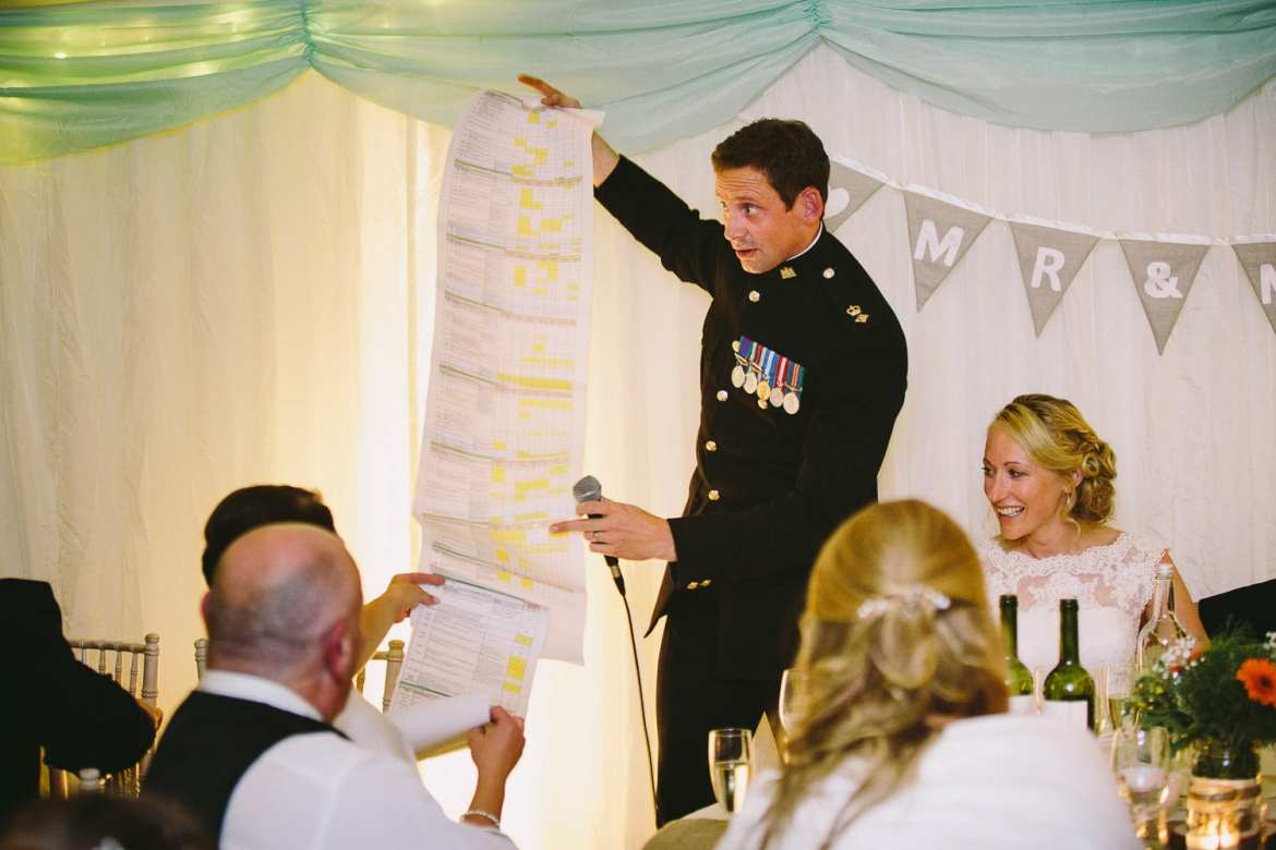 Best man showing list of spreadsheets organised by bride during his speech