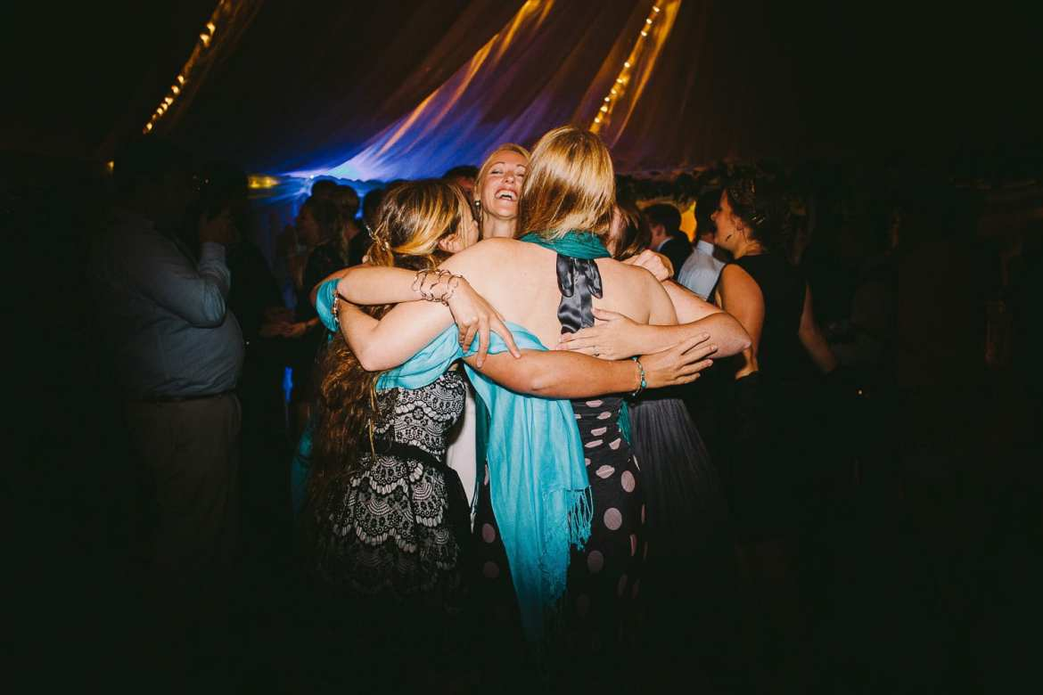 Bride hugging her friends on dancefloor