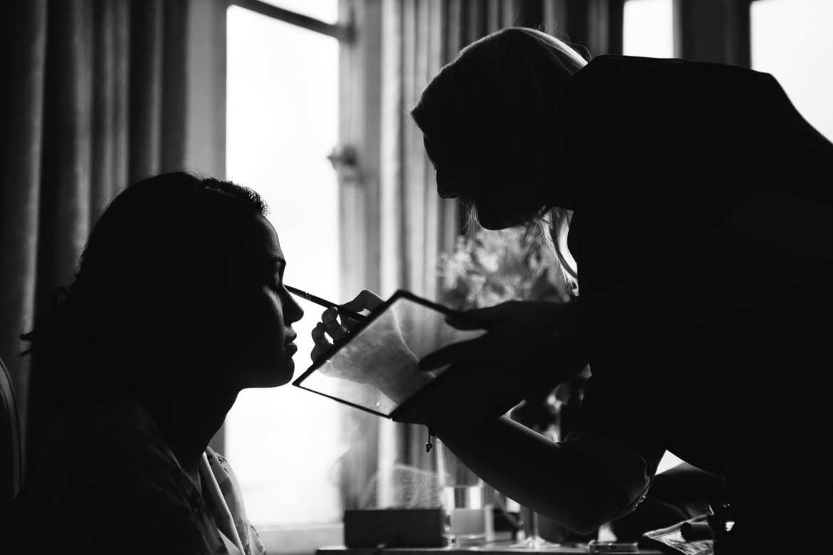 A silhouette of the bride having makeup done