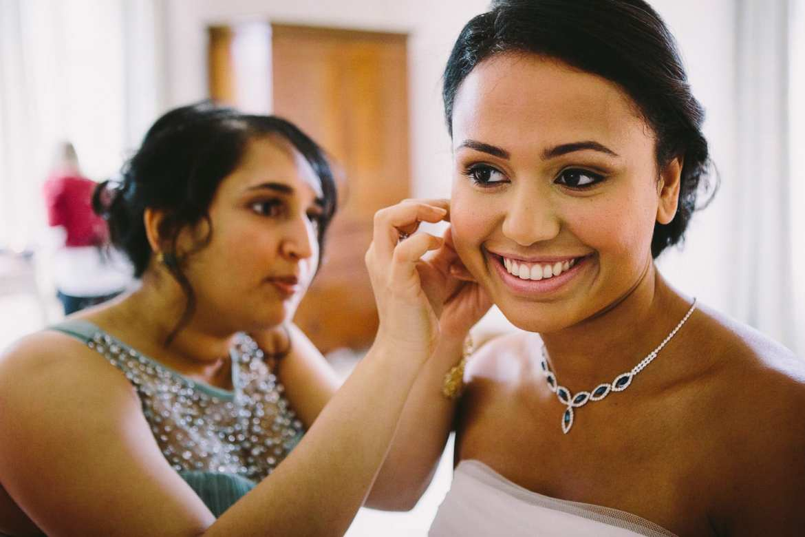 A bridesmaid helping the bride with her earrings