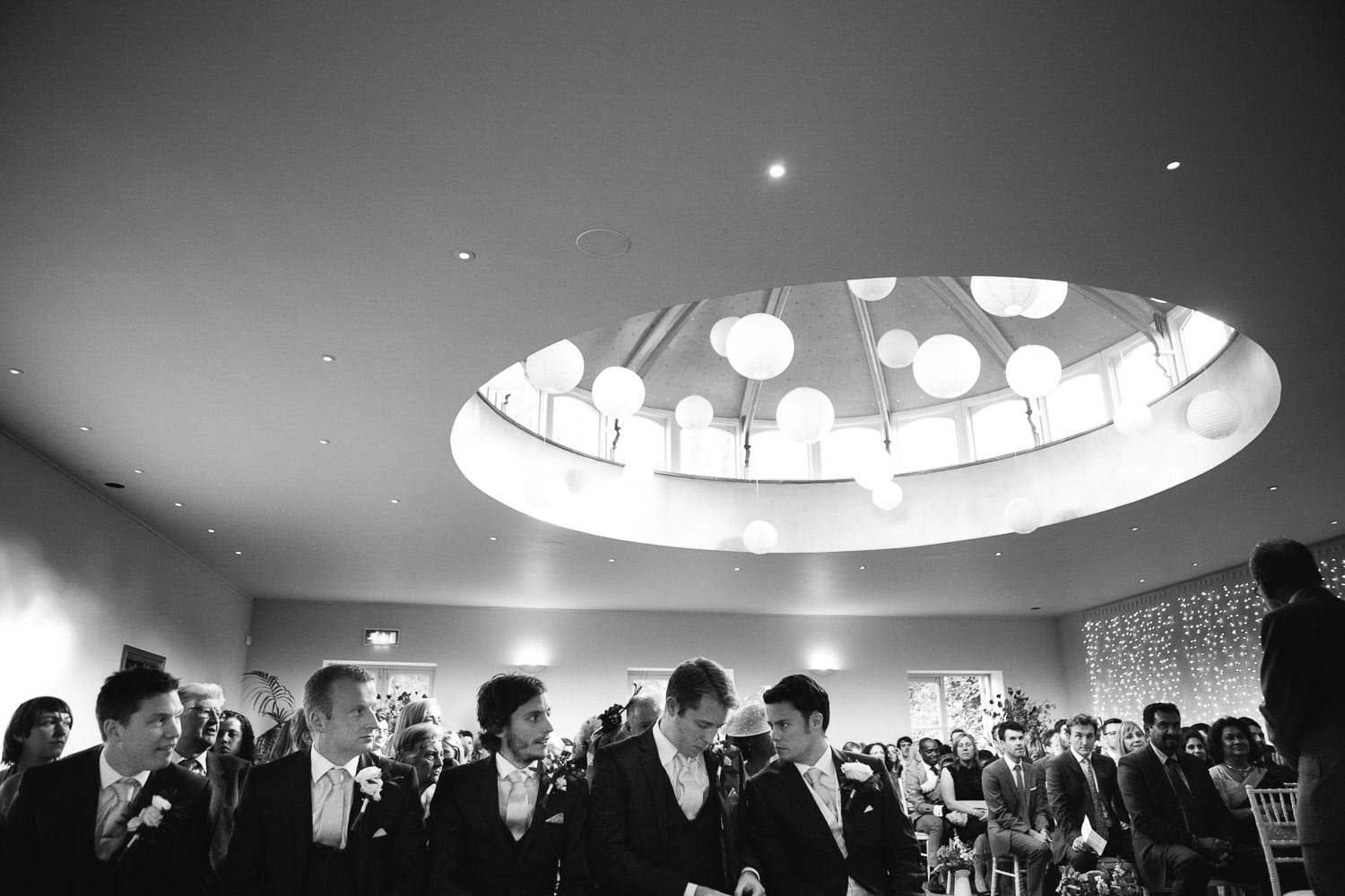 Groom and groomsment prepare for the bride's entrance in the main hall