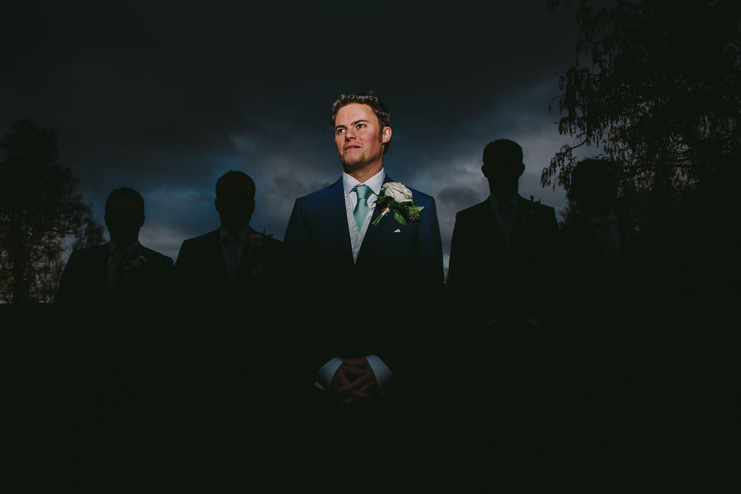 The groom stands in front of the silhouettes of his groomsmen