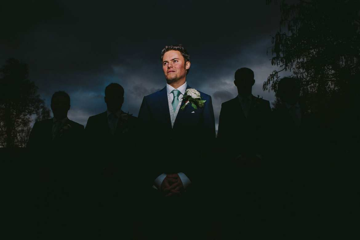 A portrait of the groom with the groomsmen in silhouette behind him