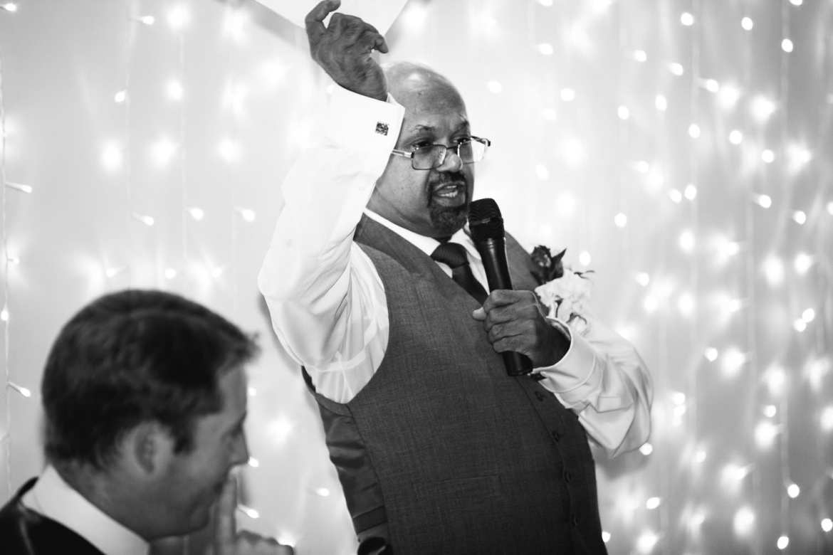 The father of the bride waves his speech notes in the air