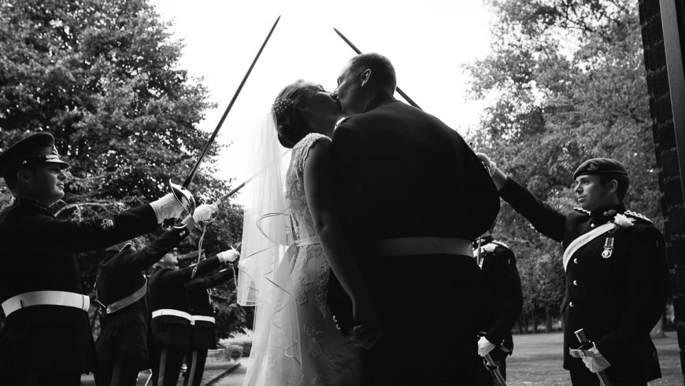 The newlyweds pause and kiss in front of the military honour guard