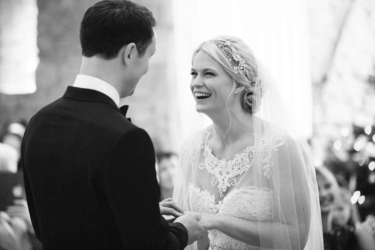 Black and white image of bride and groom ring exchange
