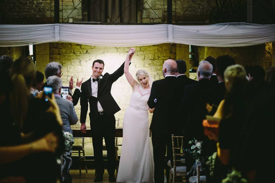 Bride and groom with their hands in the air before ceremony exit