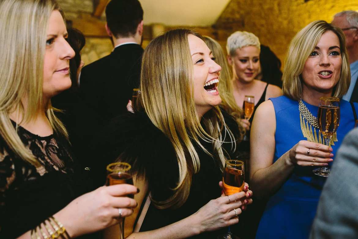 Guests laughing and enjoying pink champagne