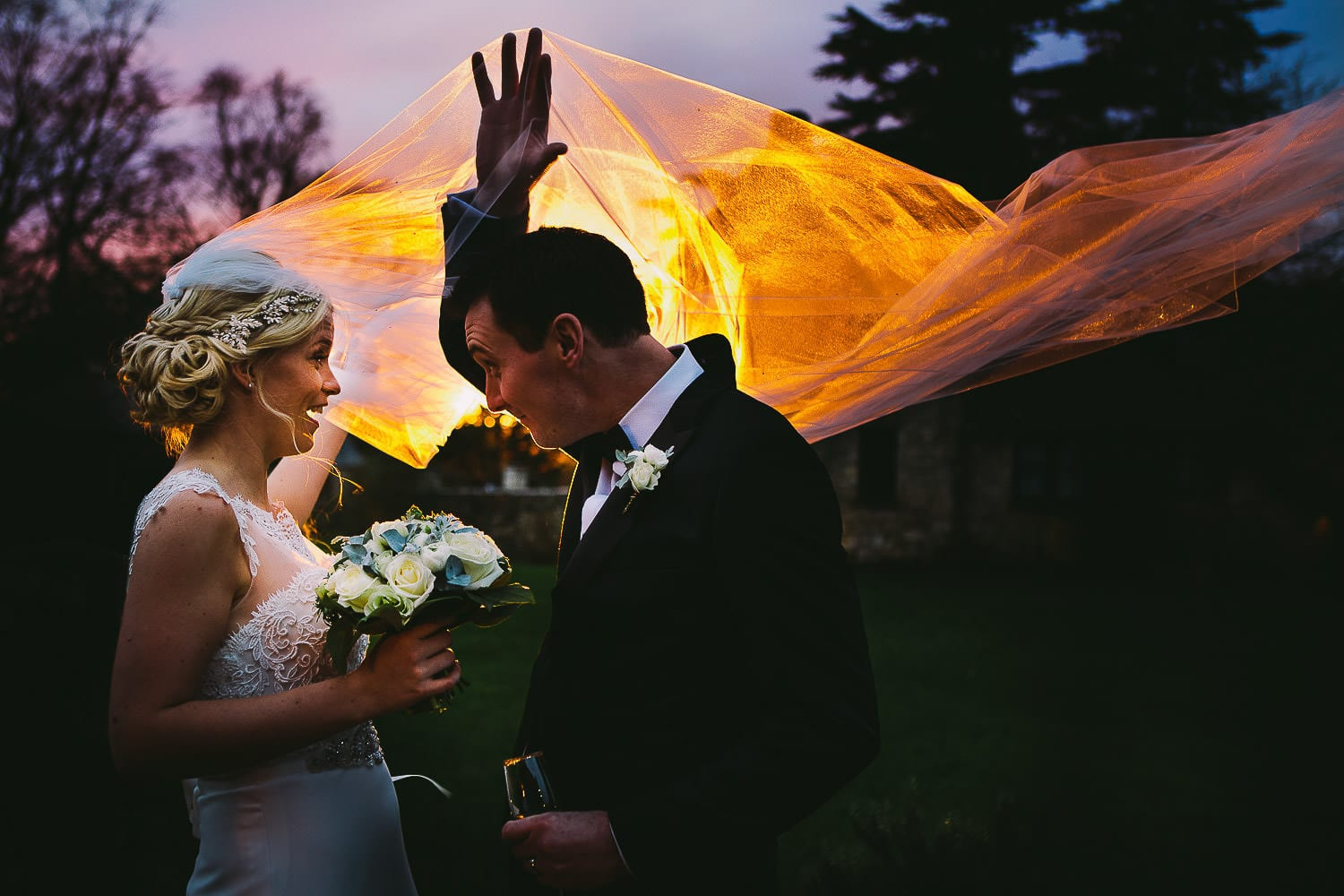 Image of the bride's veil blowing over grooms head in the sunset