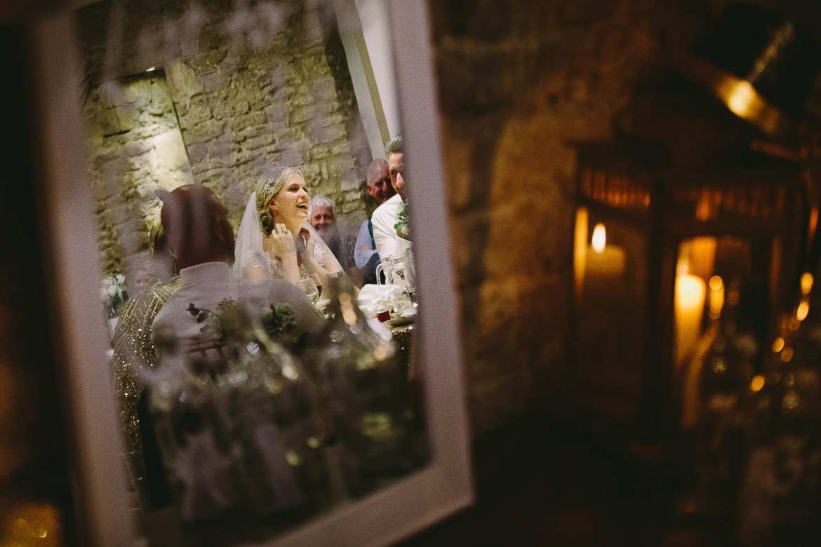 Image of the bride in a mirror during the speeches