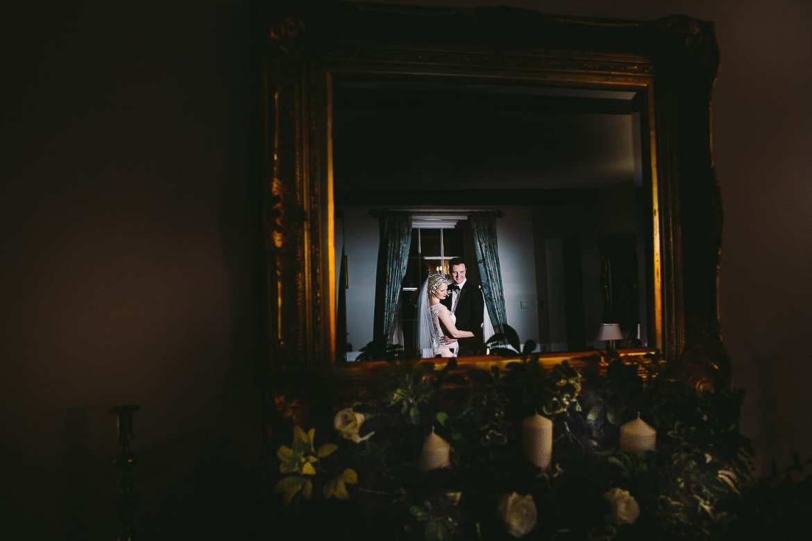 Portrait of bride and groom in the mirror in the lounge