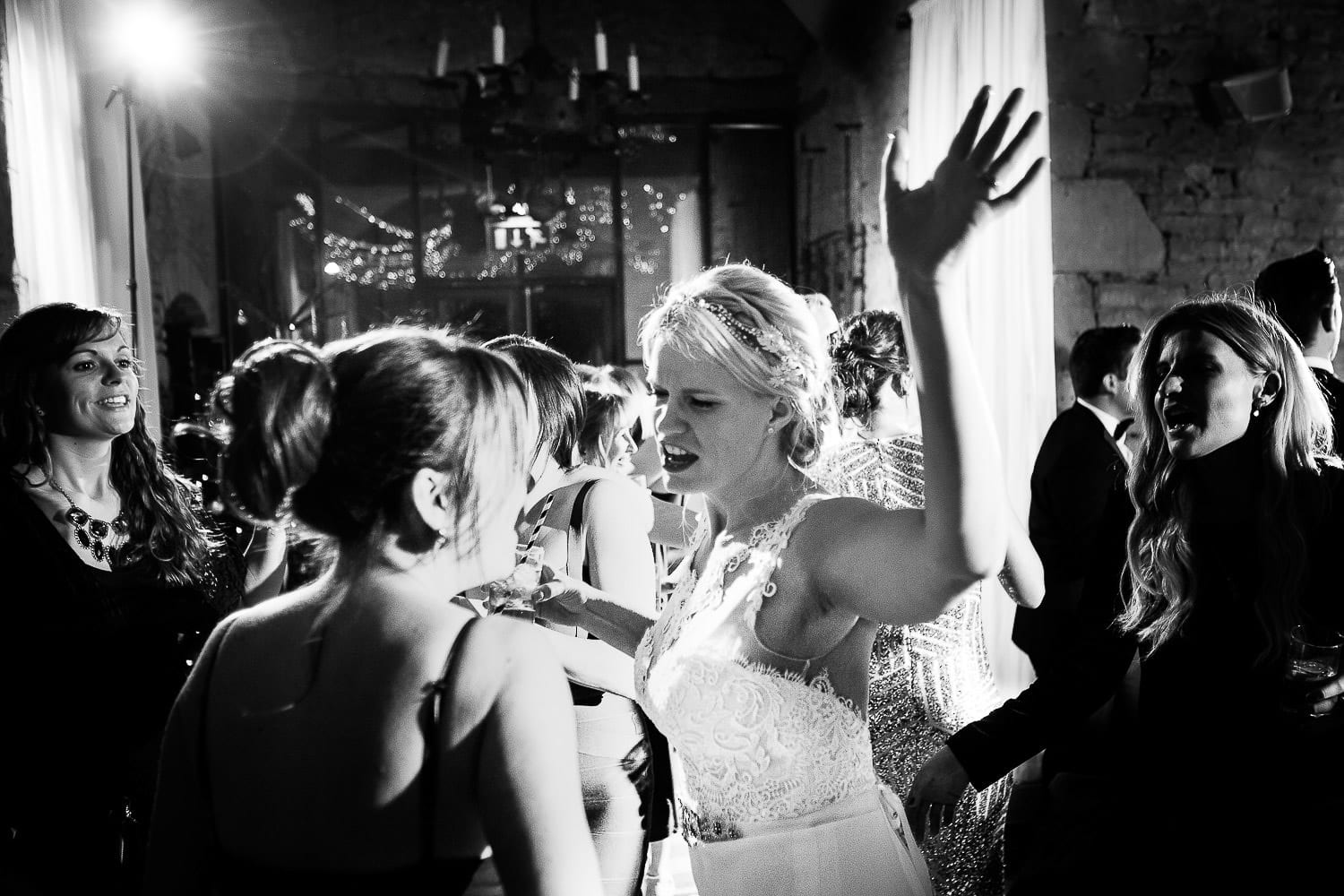 Black and white image of bride and guests dancing