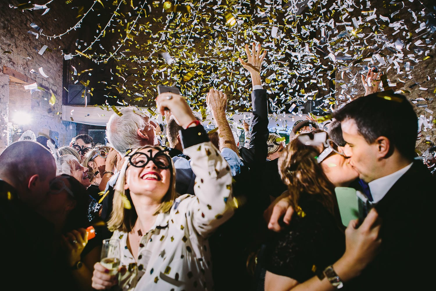 Confetti cannons going off at midnight over guests on the dance floor
